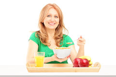 Smiling woman eating cereals and fruit for breakfast. On white background Stock Photo