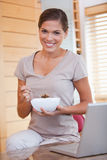 Smiling woman eating cereals next to her laptop Stock Photos