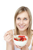 Smiling woman eating cereals with strawberries Royalty Free Stock Photo