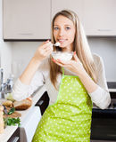 Smiling woman eating cottage cheese Stock Photo