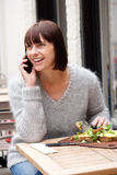 Smiling woman eating food and talking on mobile phone Royalty Free Stock Images