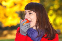 Smiling woman eating fresh apple in autumn park Stock Images