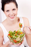 Smiling woman eating fresh salad Stock Images