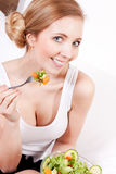 Smiling woman eating fresh salad Stock Image