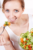Smiling woman eating fresh salad Stock Photos