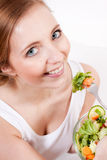 Smiling woman eating fresh salad Royalty Free Stock Photos