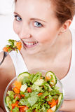 Smiling woman eating fresh salad Royalty Free Stock Image