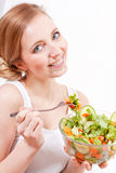 Smiling woman eating fresh salad Royalty Free Stock Images