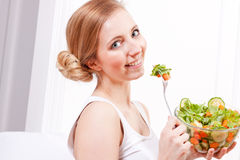 Smiling woman eating fresh salad Royalty Free Stock Photo