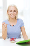 Smiling woman eating fruits with tablet pc at home Royalty Free Stock Image