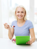 Smiling woman eating fruits with tablet pc at home Stock Images