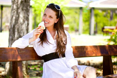 A smiling woman is eating an ice cream Stock Image