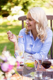 Smiling woman eating pie at summer garden party Stock Photo