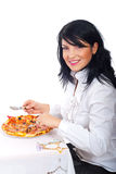 Smiling woman eating pizza at table stock image