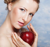 Smiling woman eating red apple Stock Images