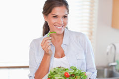 Smiling woman eating a salad Stock Photos