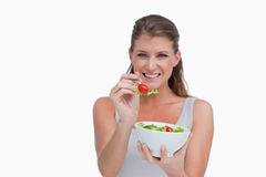 Smiling woman eating a salad Stock Images