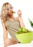 Smiling woman eating salad Stock Image
