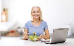Smiling woman eating salad with laptop on kitchen Stock Photo