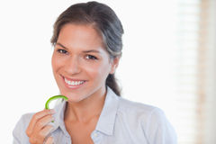 Smiling woman eating a slice of pepper Royalty Free Stock Photos
