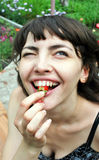 Smiling woman eating strawberries Stock Photos