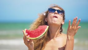 Smiling woman eating watermelon on beach. Woman eating tasty summer fruit. Happy summer time. Smiling woman eating watermelon on beach. Woman eating tasty stock video