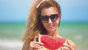 Smiling woman eating watermelon on beach. Woman eating tasty summer fruit. Happy summer time. Smiling woman eating watermelon on beach. Woman eating tasty stock footage