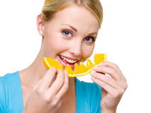Smiling woman eats the fresh orange royalty free stock images