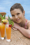 Smiling woman at edge of swimming pool next to tropical drinks Stock Photo