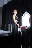 Smiling Woman in Elegant Black Dress at her Room Stock Image