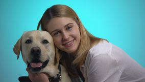 Smiling woman embracing cute labrador dog, looking at camera, pet is best friend. Stock footage stock video
