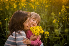 Smiling woman embracing her cute daughter, outdoors. Stock Photography