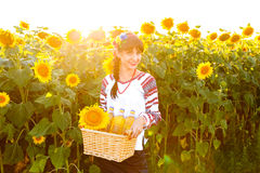Smiling woman in embroidery holding a basket with sunflower oil Royalty Free Stock Photo