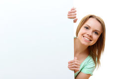 Smiling woman emerging from behind corner royalty free stock image