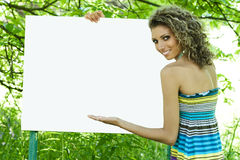 Smiling woman with empty billboard Royalty Free Stock Photos