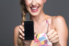 Smiling woman endorsing her smartphone. Giving a thumbs up gesture of approval as she displays the phone with the blank screen to the viewer, selective focus royalty free stock images