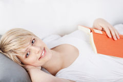 Smiling woman enjoying a book on the sofa Royalty Free Stock Images