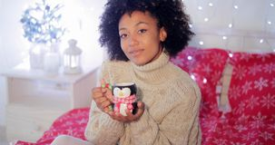 Smiling woman enjoying a cup of Christmas coffee Royalty Free Stock Photography