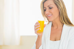 Smiling woman enjoying a glass of orange juice Royalty Free Stock Photos
