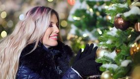 Smiling woman enjoying holidays touching big ball decoration at Christmas tree surrounded by snow stock footage