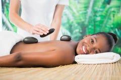 Smiling woman enjoying a hot stone massage Royalty Free Stock Photo