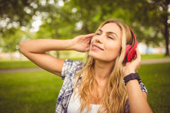 Smiling woman enjoying music with eyes closed at park Royalty Free Stock Image