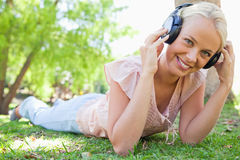 Smiling woman enjoying music on the grass Stock Photography