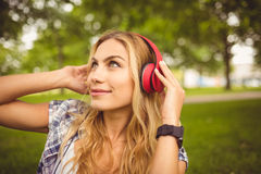 Smiling woman enjoying music at park Royalty Free Stock Photography