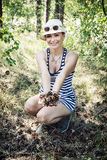 Smiling woman enjoying the pine cones in the forest by summer Stock Image