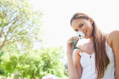 Smiling woman enjoying the smell of a flower in the park Royalty Free Stock Images