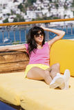 Smiling  woman enjoying the summer vacation lying on a sunbed in a sea bar Royalty Free Stock Images