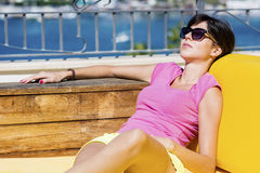 Smiling  woman enjoying the summer vacation lying on a sunbed in a sea bar. Brunette  woman enjoying the summer laying on sunbed on a sea background Royalty Free Stock Photo