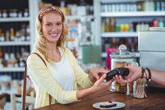 Smiling woman entering pin number into machine at counter Royalty Free Stock Photos