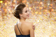 Smiling woman in evening dress from back. People, holidays and glamour concept - smiling woman in evening dress from back over golden lights background Stock Image